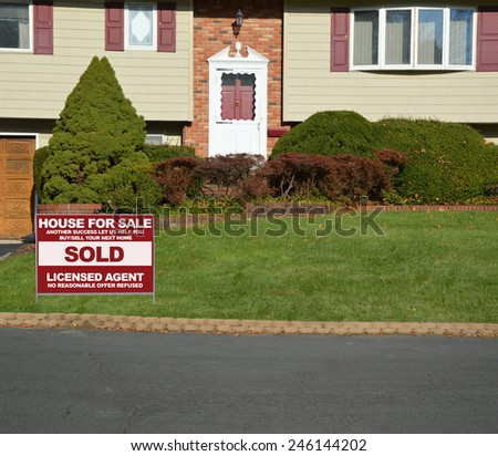 Real estate sold (another success let us help you buy sell your next home) sign Suburban High Ranch brick landscaped home with cobble stone curb sunny autumn day residential neighborhood USA - stock photo