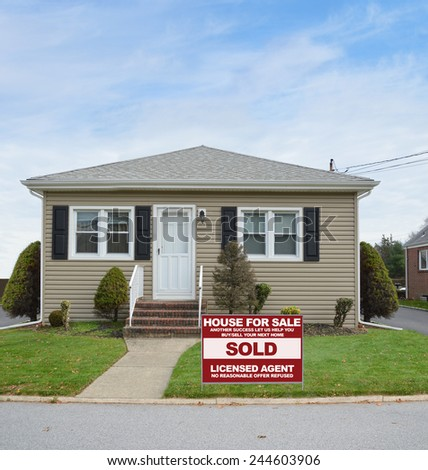 Real Estate sold (another success let us help you buy sell your next home) sign Suburban Tan Bungalow home autumn day residential neighborhood USA blue sky clouds