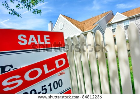Real estate sold insert on Realtor for sale sign and white picket fence at a selling suburban house after a successful resale brokerage transaction in the residential multiple listing service - stock photo