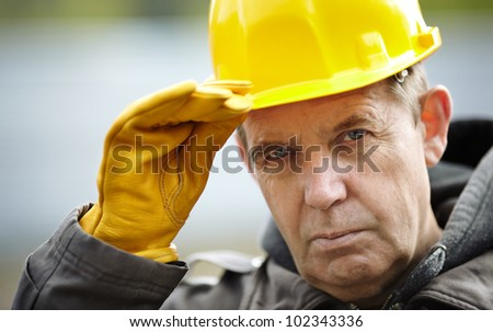 real experienced builder with yellow hardhat, natural light - stock photo