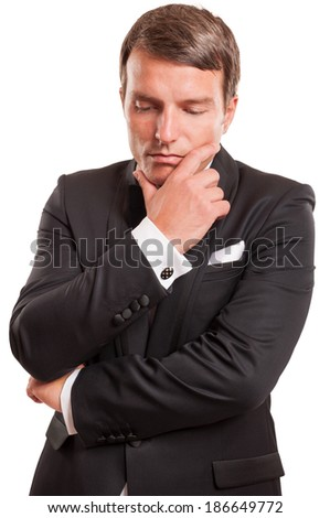 Real gentleman thinking at business while is wearing an elegant tuxedo, isolated on a white background