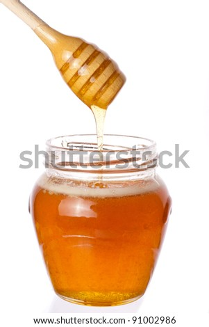Real honey with stick in a jar isolated on white - stock photo