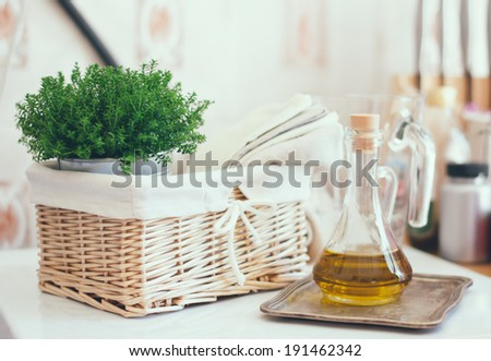 Real kitchen arrangement: vintage wicker basket, house plant, stack of linen napkins  and a bottle of olive oil on white table. - stock photo