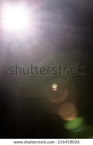 Real Lens Flare and Dusty Atmosphere - Studio Shot - Isolated on Black Background - stock photo