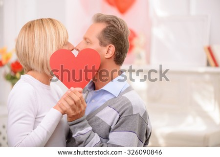 Real love. Loving agreeable adult couple holding heart and kissing while expressing truthful feelings - stock photo