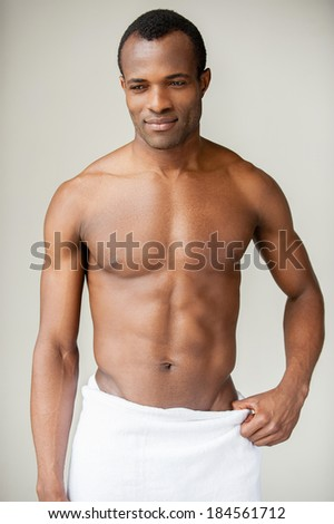Real macho. Young shirtless African man wrapped in towel looking away and smiling while standing against grey background - stock photo