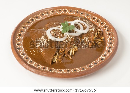 Real Mexican Enchiladas This enchiladas where made by a Mexican chef using exquisite 'mole' sauce from the state of Puebla in Mexico. They are served only with onion rings and sesame seeds. - stock photo