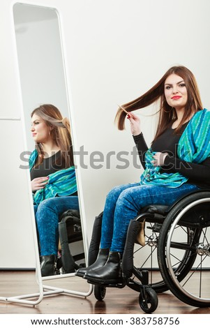 Real people, disability and handicap concept. Teen girl handicapped woman sitting on wheelchair in front of mirror combing hair. Daily personal care