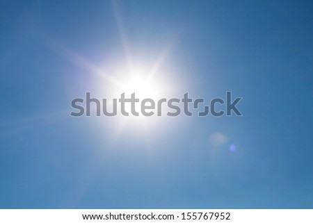 Real photo lens glow effect of sun on clear blue sky - stock photo