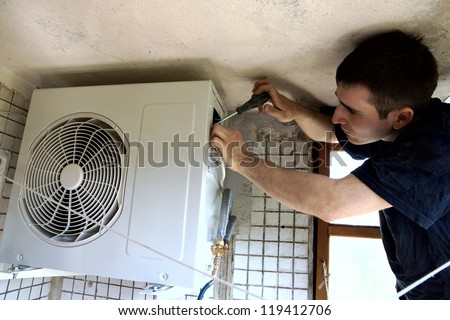real photo of installation of the conditioner, the worker connects electric wires - stock photo