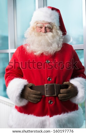 Real Santa Claus standing at airport and waiting for his flight - stock photo