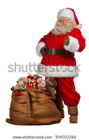 Real Santa Claus thumbs up near big bag full of gifts, isolated on white background. Full length portrait - stock photo