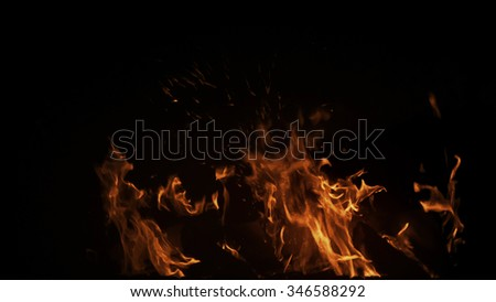 Real shot fire with particles on black background, perfect for digital composition. - stock photo