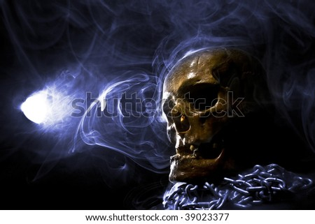 real skull with chain in abstract smoke - stock photo