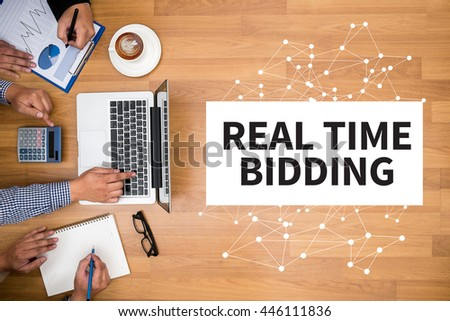 REAL TIME BIDDING Business team hands at work with financial reports and a laptop - stock photo