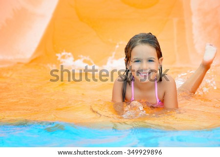 Real toddler girl enjoying her summer vacation on water slide at aquapark