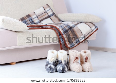 Real wool slippers and blanked on sofa, fluffy rustic style - stock photo