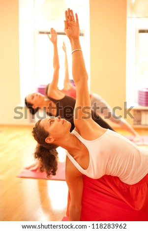 Real yoga instructor at classroom showing exercise - stock photo