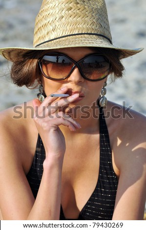 real young woman smokes on the beach wearing hat and sunglasses - stock photo
