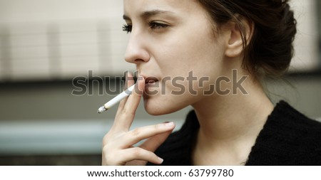 real young woman smokes on the street, selective focus - stock photo