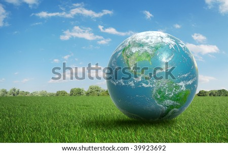 Realistic Earth on a green  field of grass - stock photo
