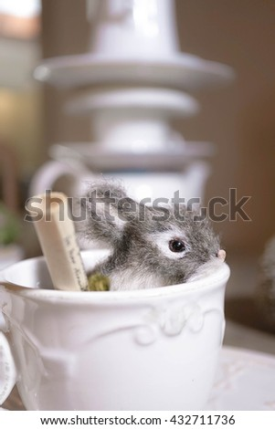 Realistic Rabbit, Animal Replica Prop Fur Toy, for Decoration. Rabbit inside a vintage teacup with small invitation scroll. Concept of Alice in Wonderland's Tea Party (The Mad Tea Party).  - stock photo