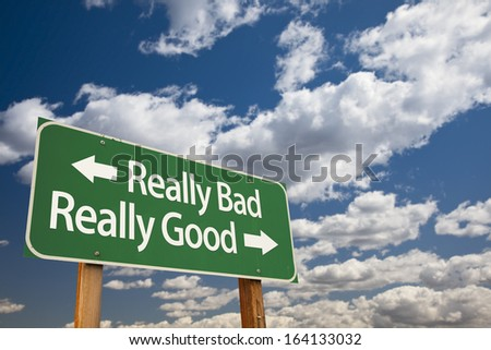 Really Bad, Really Good Green Road Sign with Dramatic Clouds and Sky. - stock photo