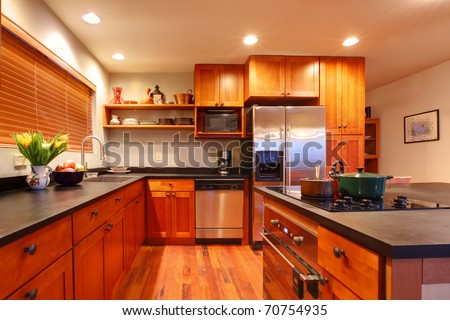 Really nice kitchen with cherry wood and hardwood floor - stock photo