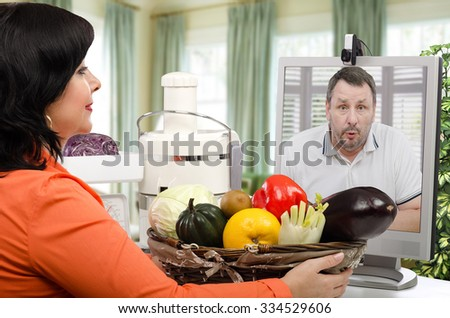 Really shocked man is looking from the monitor screen to fresh vegetables. The man taking the first on-line lesson of a healthy nutrition - stock photo