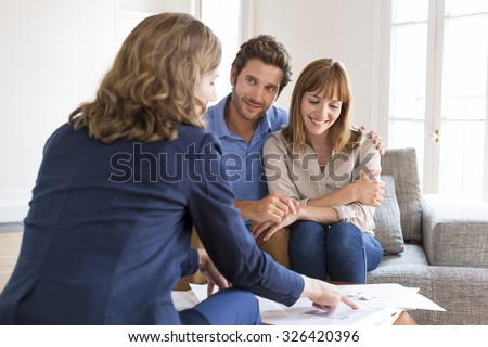 Realtor agent presenting a contract for apartment investment to futur owners couple - stock photo