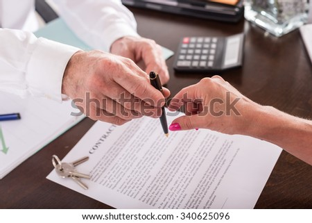 Realtor giving his client a pen to sign the contract - stock photo