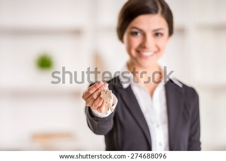Realtor is giving the keys to an apartment to clients. Focus on the keys. - stock photo