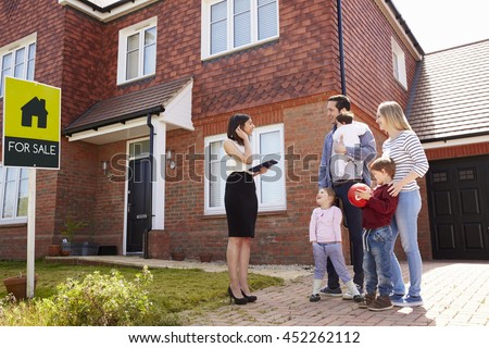 Realtor Outside House For Sale With Young Family - stock photo