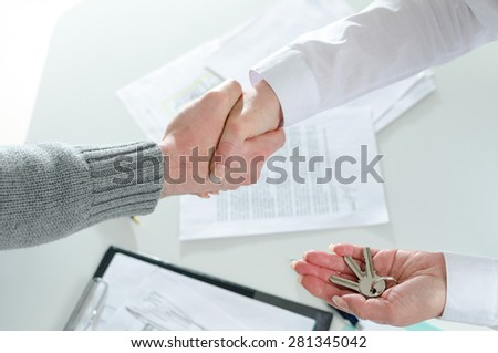 Realtor shaking hands with his client after handing over the keys - stock photo