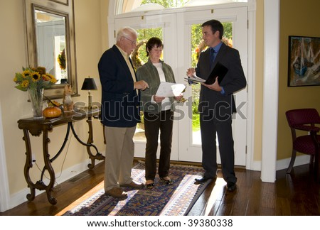 realtor showing a home to a senior couple - stock photo
