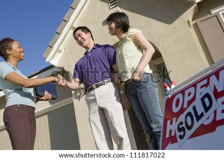 Realtor with couple buying new house - stock photo