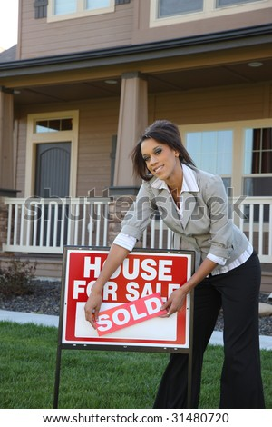 Realtor with sold sign in front of home