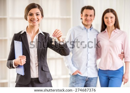 Realtor woman is holding keys and young couple on background. - stock photo