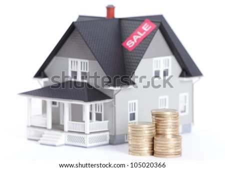 Realty concept - stacks of coins in front of house architectural model, isolated