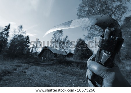 reaper concept, hand holding old scythe in late evening, on the way to old farm-house, blue toning - stock photo