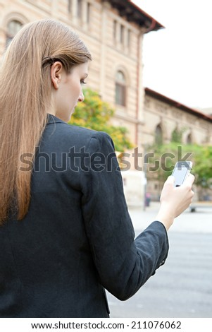Rear close up portrait view of an attractive thoughtful young businesswoman using smartphone technology in a classic city, outdoors. (Business, People, Technology) - stock photo