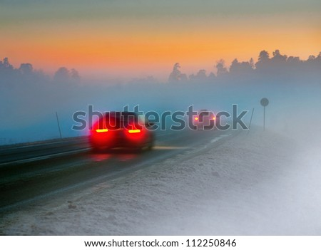 Rear lights of car on road in dark foggy winter evening - stock photo
