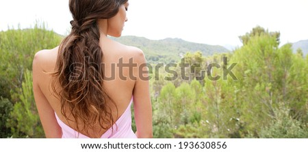 Rear panoramic view of a beautiful young woman with bare shoulders relaxing in the forest mountains contemplating nature during a calm summer holiday. Travel and healthy lifestyle and beauty outdoors. - stock photo