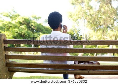 Rear portrait of young african woman sitting on a park bench using cell phone - stock photo