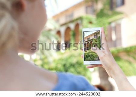 Rear portrait view of young tourist girl holding up a smartphone device to point and take pictures of monument while visiting a destination city on holiday. Vacation travel and technology networking.