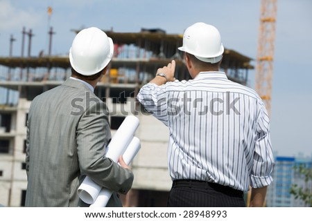 Rear shot of boss pointing at construction with worker near by - stock photo
