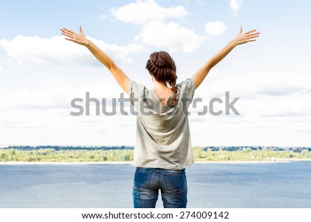Rear shot of young woman raising arms up towards blue sky and river. - stock photo