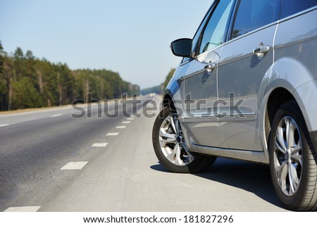 Rear-side perspective view of car on highway - stock photo