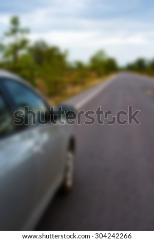 Rear side perspective view of car on road countryside. blur background - stock photo