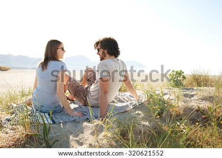 Rear side portrait of a young tourist couple sitting together on a white sand beach with dunes on a sunny day on holiday, outdoors. Travel and vacation lifestyle, nature living spacious exterior. - stock photo